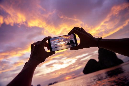 Hands take mobile photo beautiful sunset