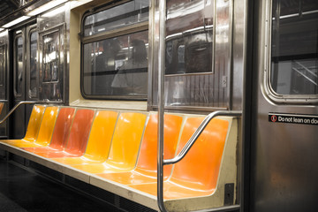 Fotobehang Amerikaanse Plekken View inside New York City subway train car with vintage orange, yellow and red color seats