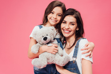 smiling daughter hugging mother and holding soft toy isolated on pink