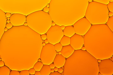 Abstract background of orange oil drops on water