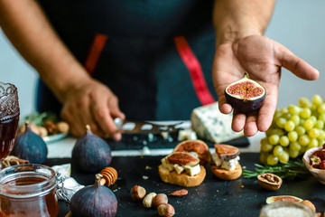 Figs fruit in hands in the kitchen. Bruschettas with figs, Blue cheese and walnuts on grilled crusty bread. Food recipe concept