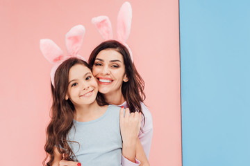 beautiful woman in easter bunny ears hugging child and looking at camera on blue and pink background