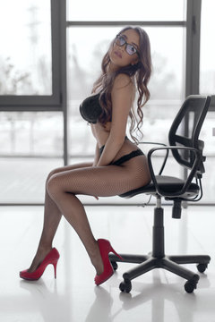 Sexy girl secretary in black lingerie and glasses poses sits sitting in an office chair