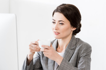 attractive businesswoman in grey suit sitting at table with computer and holding cup of coffee in office