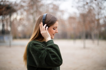 Side view of pretty young female in headphones smiling and listening to music while standing on blurred background of autumn park