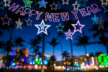 Festive Happy New Year message with stars sparkling above a silhouette view of palm trees and the colorful neon lights of Miami