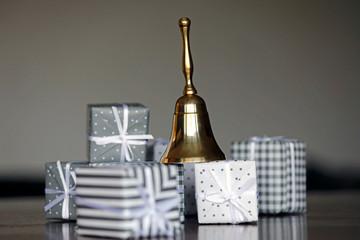 Im Vordergrund stehen hübsch verpackte Geschenke im Hintergrund eine Weihnachtsglocke die zur Bescherung ruft