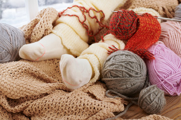 Child legs in warm socks are on a window sill with wool yarns.