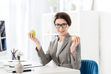 attractive businesswoman holding apples and looking at camera in office