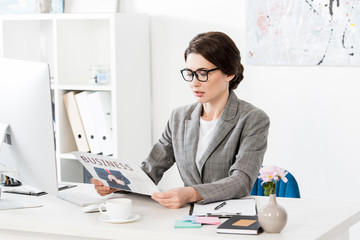 attractive businesswoman in glasses reading newspaper in office