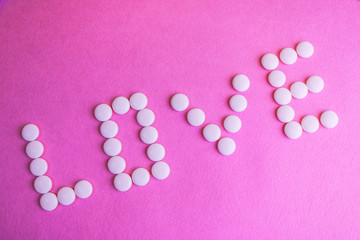 Beautiful inscription love made from white round smooth medical pills, vitamins, antibiotics and copy space on a bright purple pink background. Flat lay