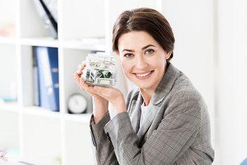 attractive happy businesswoman holding glass jar with money in office and looking at camera