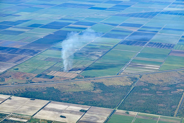 Aerial view of a sugar cane field near Lake Okeechobee, Florida being burned, creating air pollution.