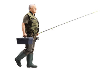 Mature fisherman walking with a fishing rod and a box