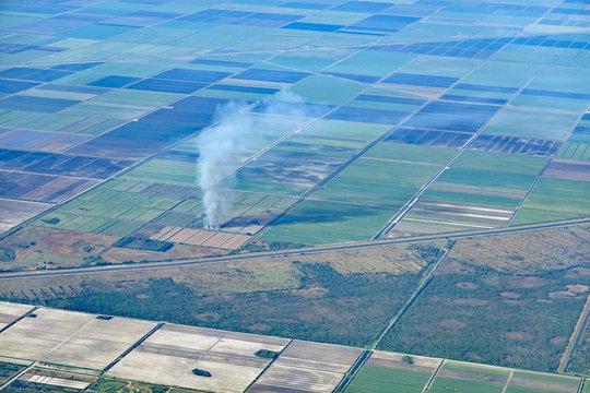 Aerial view of a sugar cane field near Lake Okeechobee, Florida being burned, creating air pollution.