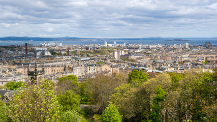 Landscape of the city of Edinburgh in Scotland. Cityscape with medieval and modern architecture on a cloudy day, view from Calton Hill.