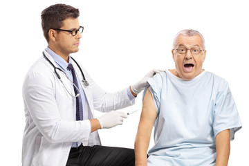 Young male doctor giving an injection shot to a scared mature