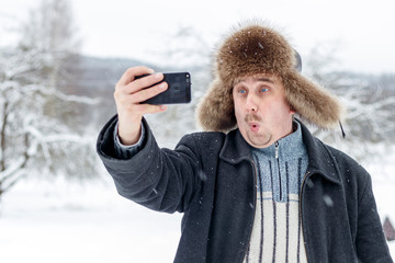 A young man is surprised at the camera, makes a selfie in a snowy winter forest. the guy on the street. on it hats made of natural fur. there is toning