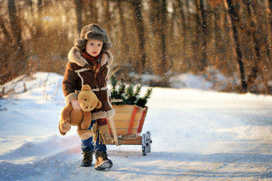Child in winter. Fun little boy in the snow. The child is playing outside. Winter background. Beautiful, original winter photos.