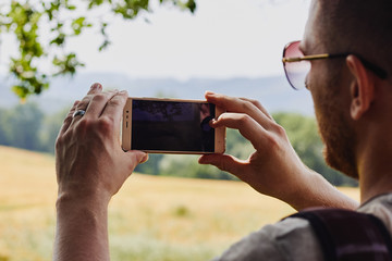 Young man takes photo of landscape using a smartphone