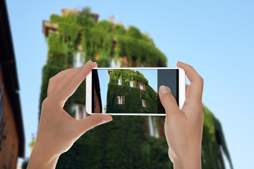 A man is making a photo of the building is completely overgrown with vine lightly in Trastevere district, Rome, Italy on a mobile phone