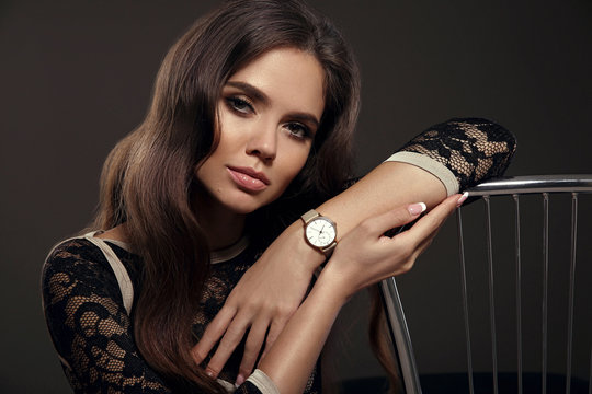 Elegant lady with Watch on hand. Beautiful woman with long healthy wavy hair style posing in studio on dark background.