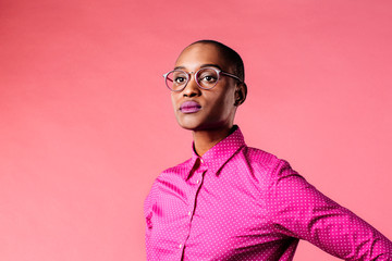 Portrait of a young woman with glasses and pink shirt, isolated on pink studio background