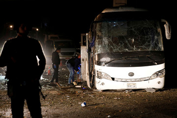Police officers inspect a scene of a bus blast in Giza