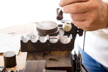 Złotnik w pracowni jubilerskiej wykonuje biżuterię.