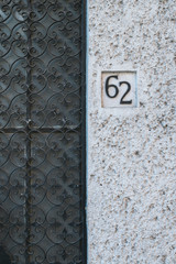 Board with 62 house number on wall