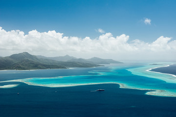 Aerial view on lagoon of Raiatea island in French Polynesia with blue and turquoise water, barrier reef, blue sky, hills with tropical forest and white clouds