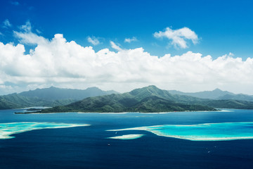 Scenic aerial view on lagoon with blue and turquoise water, barrier reef, blue sky and white clouds of Raiatea island in French Polynesia