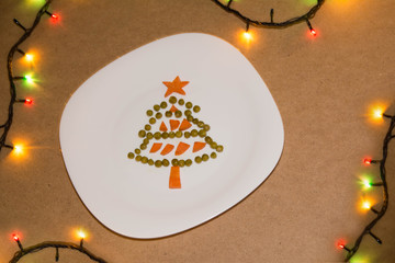 Unusual tasty Christmas tree made of peas and carrots, New Year food background top view. holiday, celebration, food art concep