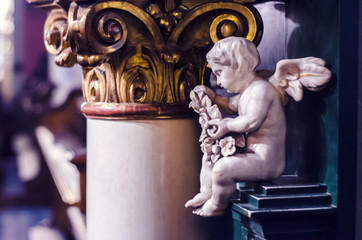 An angel medieval sculpture made of white marble on the background of a gold-plated caption.
