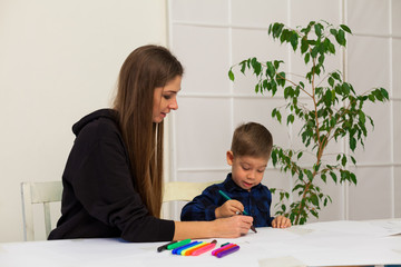 mother and young son draws a picture at the table