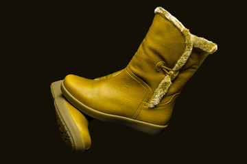 Yellow leather boot on black background