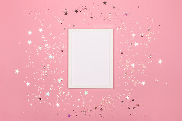 Festive background with blank white photo frame on pink pastel with scattered confetti. Mock up for photo or text. Top view. Flat lay style.