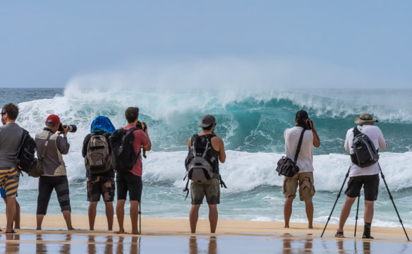 People admiring the big waves and photographers taking pictures of the big waves of Pipeline beach in Hawaii during the winter season.