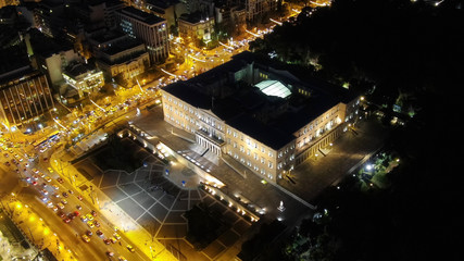 Aerial drone night shot from famous illuminated Greek Parliament  building near Syntagma square, Athens historic centre, Attica, Greece
