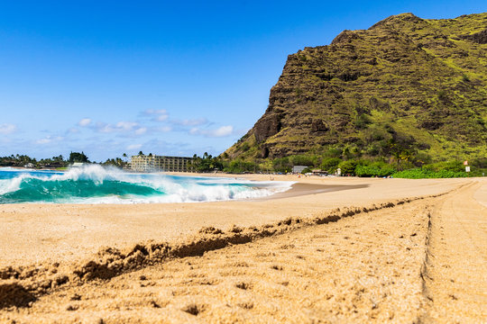 Sunny day at Makaha beach on the west side of the island of Oahu in Hawaii amidst beautiful green mountains with volcanic formation in front of the blue sea