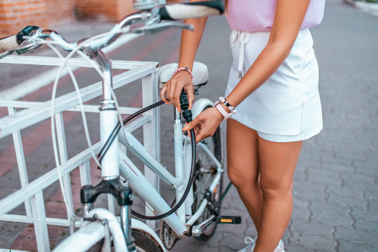 The girl defends her bike in park in summer. Removes from parking lot, uses a protective chain, sets the password, the cipher to the lock against theft of the bicycle.