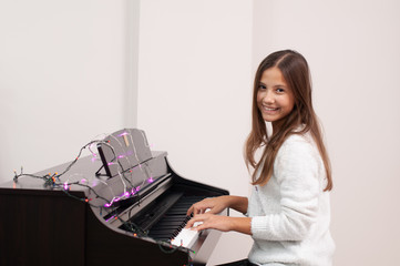 Young girl child plays piano. There are lights on the piano..