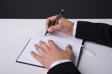 hands of a man in suit making notes