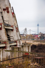 Abandoned stadium concrete reinforcement foundation construction frame shapes with tv-tower on the background
