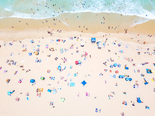 An aerial view of people on the beach with blue water on hot summer's day