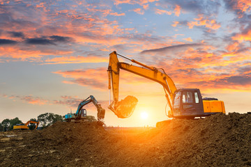 Three excavators work on construction site at sunset Fototapete