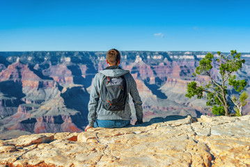 Young guy on the edge of a cliff on the Grand Canyon.