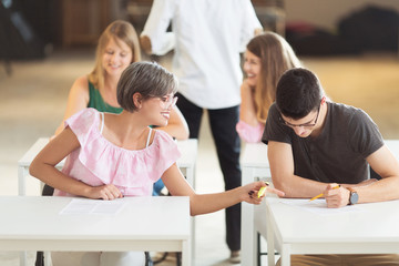 Young students sitting together and having exam in classroom