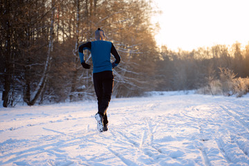 Image from back of man in sportswear, red cap on run in winter