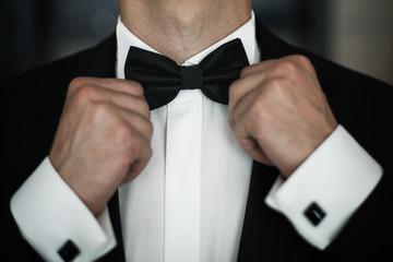 Man fies black bow tie on white shirt
